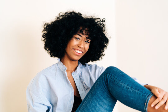 Smiling black woman with curly hair looking at camera