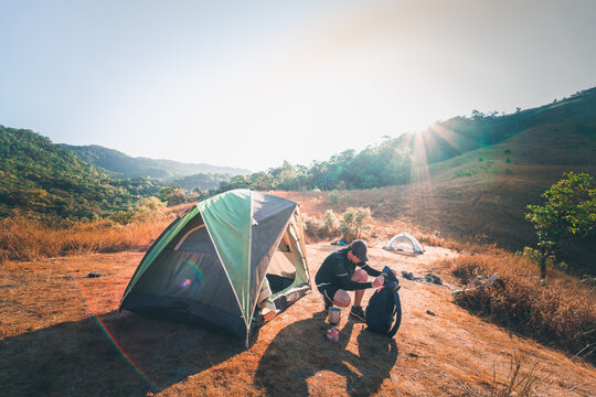 wanderlust and relax in nature with hiker man camping on top of mountain on spring and summer season