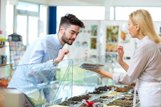 young man choosing chocolates from confectioners counter