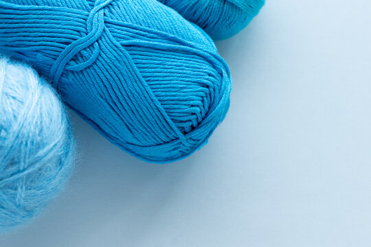 Clews of woolen nylon or acrylic yarn for knitting for handmade or hobbies lie in the corner of the frame and copy space blank or mockup for design and inscriptions with text