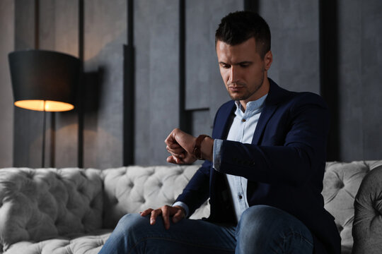 Handsome businessman checking time on sofa indoors. Luxury lifestyle