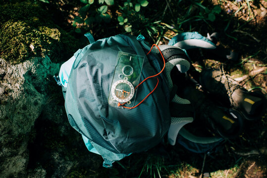 compass backpack and hiking boots on the ground in the wild