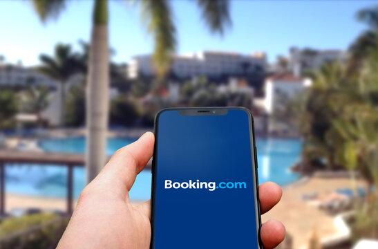Booking.com Logo wird auf einem modernen Smartphone angezeigt dahinter ein Hotel mit Pool und Palmen, Hotels, Ferienwohnungen, Flüge, Mietwagen, Urlaub, 2021