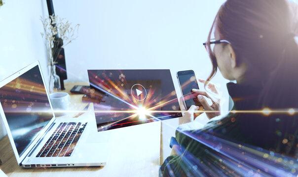 携帯電話で動画再生する女性の後ろ姿と光のCG合成イメージ