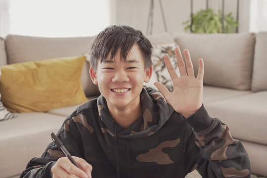 POV Portrait of Asian preteen teen boy making video calling at home, using webcam zoom online virtual class , social distancing, homeschooling, remotely  learning during covid pandemic