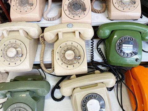Many rotary telephones arranged on shelves