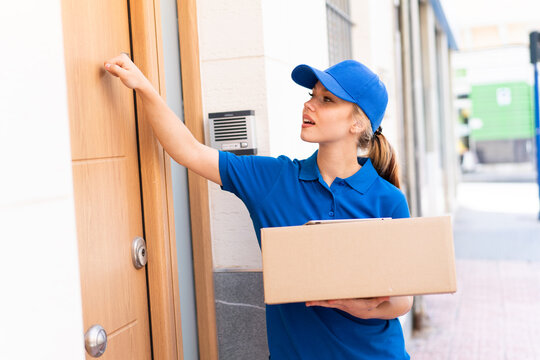 Young delivery woman at outdoors holding boxes and knocking on the door