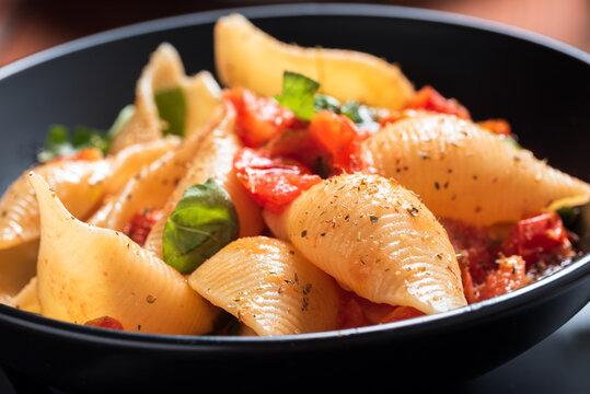 Piatto di conchiglioni con pomodoro fresco, olio di oliva, aglio, basilico fresco e origano, Dieta Mediterranea, Pasta Italiana