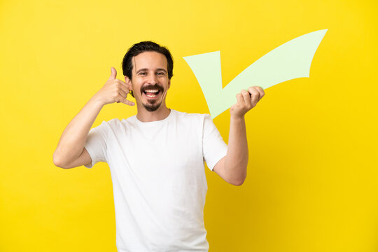 Young caucasian man isolated on yellow background holding a check icon and doing phone gesture