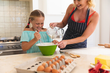 Caucasian mother and daughter baking and smiling in kitchen