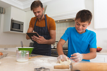 Caucasian father using tablet and son baking and smiling in kitchen
