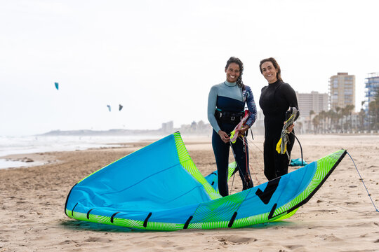 Happy diverse sportswomen with inflatable kites over sea beach