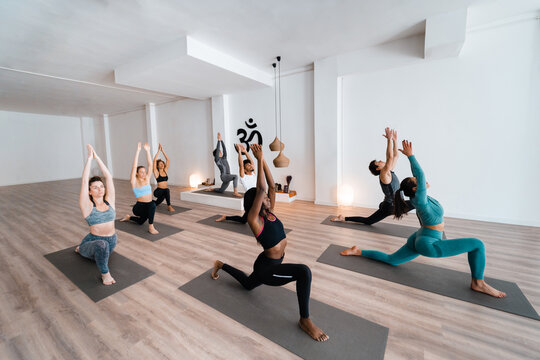 Group of multiracial people practicing yoga in Crescent Lunge pose