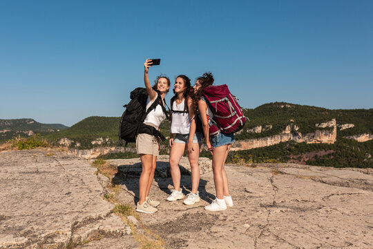 Group of traveling women taking selfie in mountains