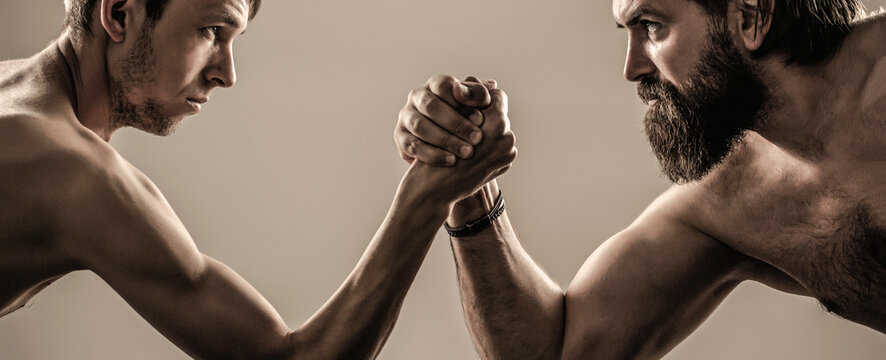 Two man's hands clasped arm wrestling, strong and weak, unequal match. Heavily muscled bearded man arm wrestling a puny weak man