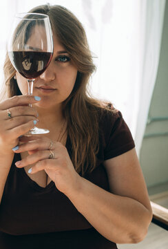 beautiful plus size woman with glass red wine. Closeup portrait of young female customer