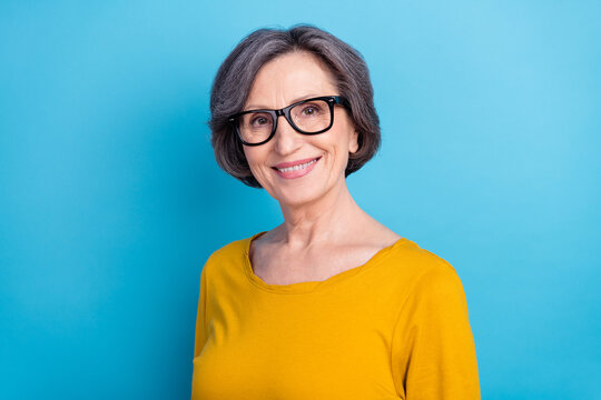Portrait of attractive cheerful content wise woman wearing specs eye sight vision view isolated over vivid blue color background