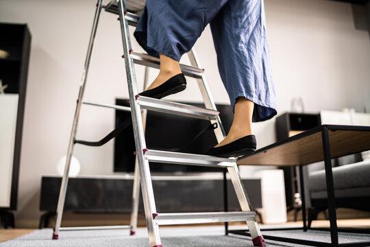 Ladder Safety. Woman Climbing Step Ladder