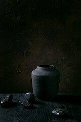 Obraz Black ceramic vase on black wooden table - fototapety do salonu