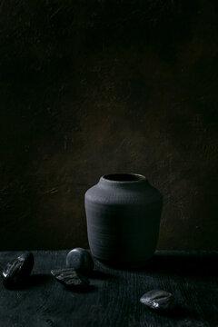 Black ceramic vase on black wooden table