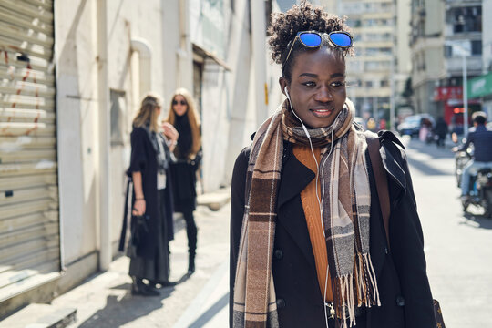 Trendy black woman on urban road against anonymous girlfriends