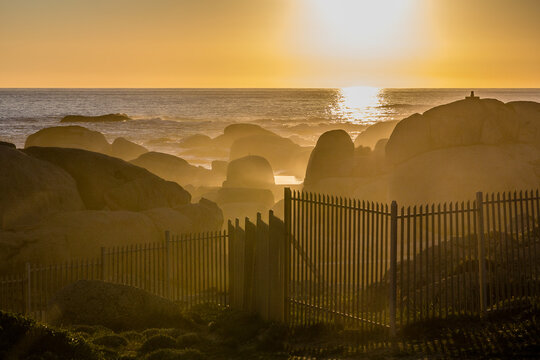 Sunset at Camps Bay. During golden hour, the mist and the waves allow Sun rays to be appreciated and behind a fence. Cape Town, South Africa, Cape of Good Hope.