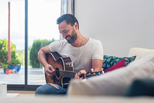Man playing guitar on couch near window at home