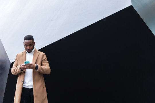 Well dressed black man chatting on smartphone near wall