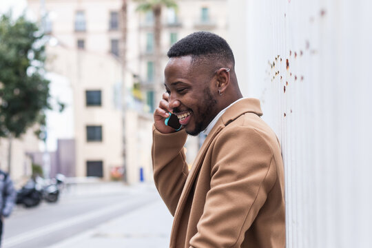 Well dressed happy black man on a phone call on smartphone near wall