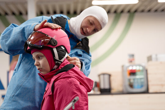 Father putting helmet on daughter before skiing
