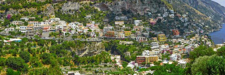 Fototapeta One of the best resorts of Italy with old colorful villas on the steep slope, nice beach, numerous yachts and boats in harbor and medieval towers along the coast, Positano. obraz