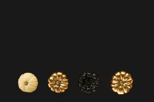 Golden, black and white pumpkin on a black background. Minimal Halloween concept. Flat lay, top view, copy space.