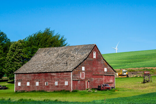 Rustic wooden red barn with modern wind turbines in the background seen from rural farming area