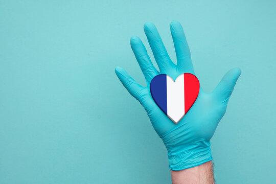 France medical health heart. Nurse hand holding country heart flag