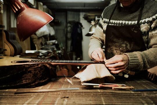 Crop artisan repairing guitar fret at workshop