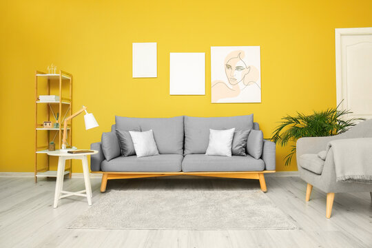 Trendy interior of living room with grey furniture and yellow wall