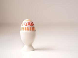 Obraz Pisanka na stole wielkanocnym, śniadanie wielkanocne, kolorowe jajko wielkanocne   - fototapety do salonu