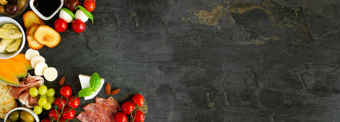 Fototapeta Italian theme charcuterie corner border against a dark slate banner background. Selection of cheese, meat and fruit appetizers. Above view with copy space. obraz