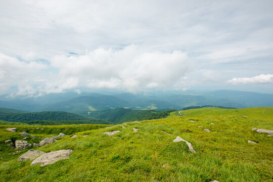 summer mountain landscape. beautiful nature scenery. stones on the grassy hills rolling in to the distant ridge beneath a cloudy sky. travel back country concept