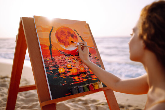 Creative female artist drawing the picture at the beach. Art, creativity and inspiration concept. Canvas Painting.