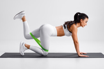Obraz Fitness woman doing kickback exercise for glutes with resistance band on gray background. Athletic girl working out donkey kicks. - fototapety do salonu