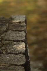 Fototapeta duży  kamienny  mur  przy  zejściu  nad   brzeg   rzeki obraz