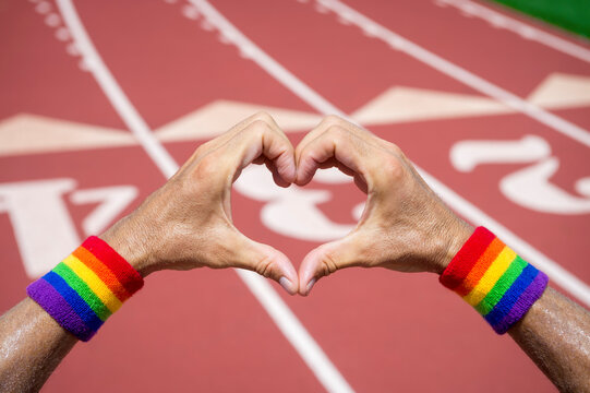 Gay athlete wearing rainbow pride wristbands making love heart hands gesture against a red athletic track background