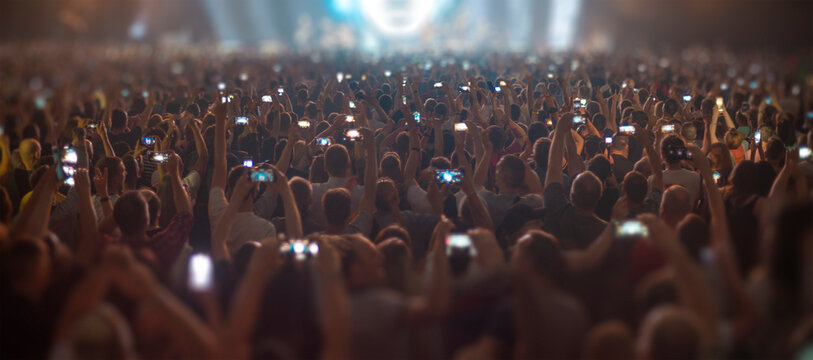 people at a concert are filming on a smartphone.