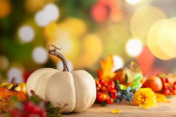 Autumn floral still life with pumpkins,berries and flowers on the table. Autumnal festive concept.