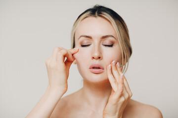 Woman doing facial gymnastics self yoga massage and tighten up face skin