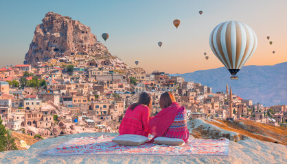 Hot air balloon flying over spectacular Cappadocia - Japanese girls watching hot air balloon at the hill of Cappadocia