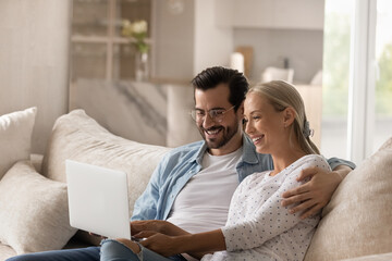 Happy wife and husband in glasses hugging, relaxing on couch with laptop, smiling young couple looking at computer screen, shopping or chatting in social network together, having fun online