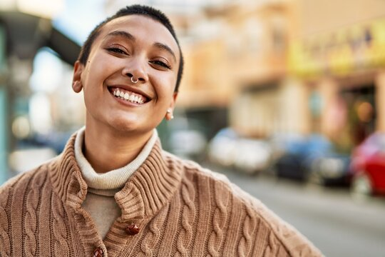 Beautiful hispanic woman with short hair smiling happy outdoors