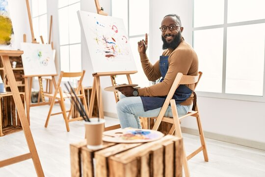 African american artist man painting on canvas at art studio surprised with an idea or question pointing finger with happy face, number one